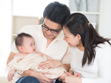 asian baby: Asian parents pampering six months old baby girl at home.