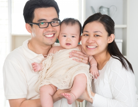 six months: Portrait of Asian parents and six months old baby girl at home. Asian family.