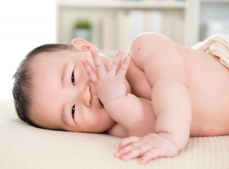 babies: Adorable zes maanden oude Aziatische baby meisje liggend op bed bijten vingers.