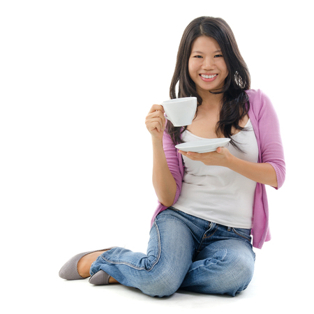 Asian female holding a cup of tea sitting over white background Stock Photo - 22617926