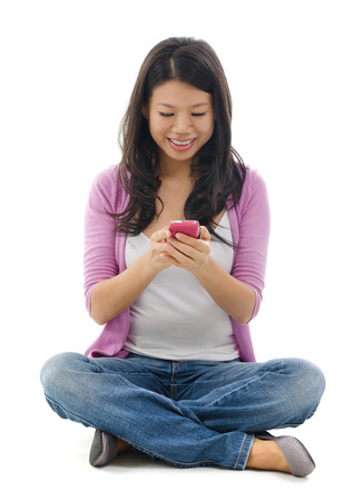 Young Woman smiling and texting on her mobile phone, sitting isolated over white background.  photo