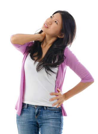 backpain: Tired Asian woman having neck and shoulder pain, standing isolated over white background. Stock Photo