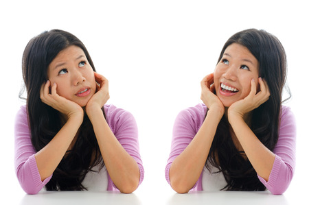 two minds: Sad and happy face expression of Asian woman, hands holding face sitting isolated over white background. Stock Photo
