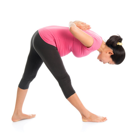 Prenatal yoga class. Full length healthy Asian pregnant woman doing yoga exercise stretching, full body isolated on white background. Yoga positions standing forward bend. photo