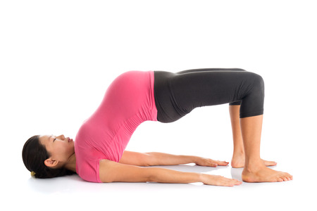 Pregnancy yoga class. Full length healthy Asian pregnant woman doing yoga exercise stretching, full body isolated on white background. Yoga bridge pose. photo