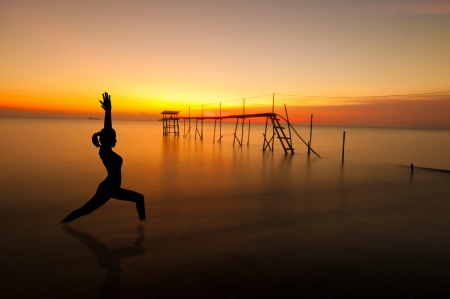 Silhouette of woman doing yoga meditation during sunrise with natural golden sunlight at beach. photo