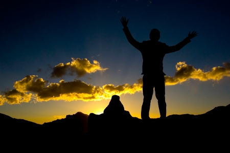 standing stones: Silhouette of businessman standing on top mountain open arms looking at the sunrise or sunset