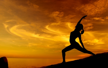 woman shadow: Silhouette of young woman doing yoga in sunrise at beach. Stock Photo