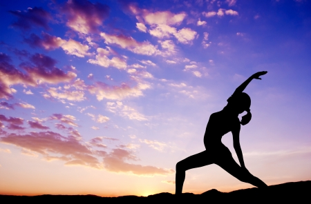 Silhouette of healthy woman doing yoga meditation during sunrise with natural sunlight outdoor. photo