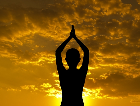 Silhouette of woman doing yoga meditation during sunset with natural golden sunlight outdoor. photo