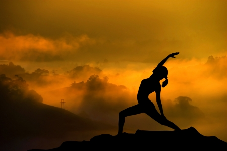Silhouette of woman doing yoga meditation during sunrise with natural golden sunlight on mountain. photo