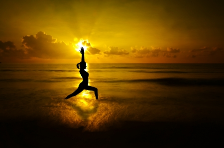 Silhouette of female doing yoga meditation during sunrise with natural golden sunlight at beach. photo