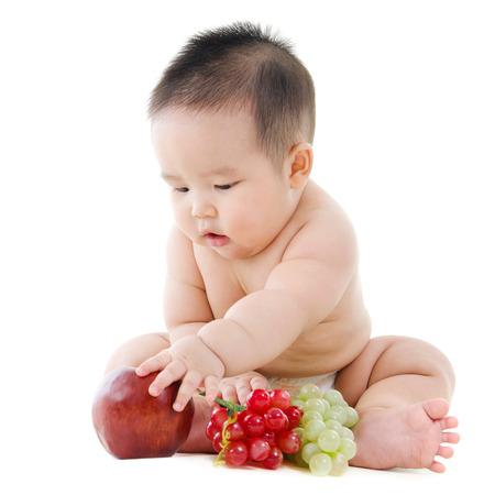 Full body Aziatische Vegetarische baby spelen met fruit zitten op een witte achtergrond Stockfoto