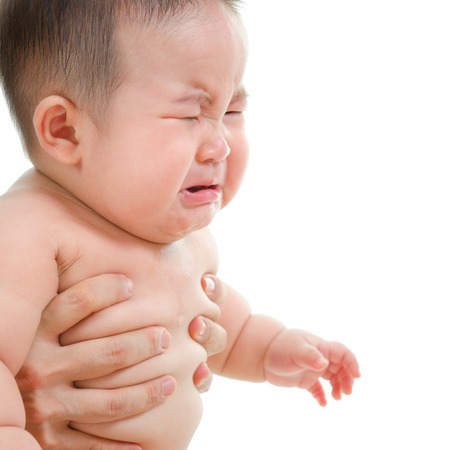 Sad Asian baby boy crying, sitting isolated on white background photo