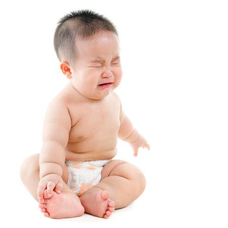 ni�os enfermos: Todo el cuerpo malestar Beb� asi�tico llorando, sentado sobre fondo blanco