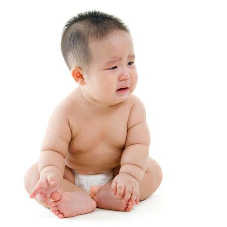 Todo el cuerpo triste Bebé asiático llorando, sentado sobre fondo blanco Foto de archivo
