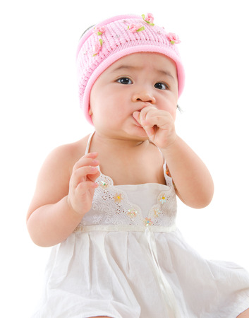 Portrait of cute Asian baby girl, eating on her own,  isolated on white background photo