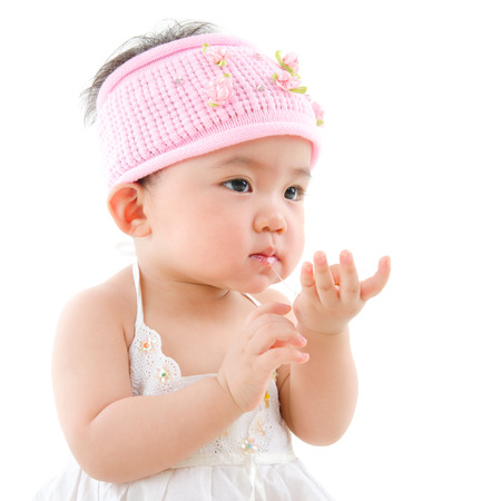Portrait of cute Asian baby girl  eating,  isolated on white background photo