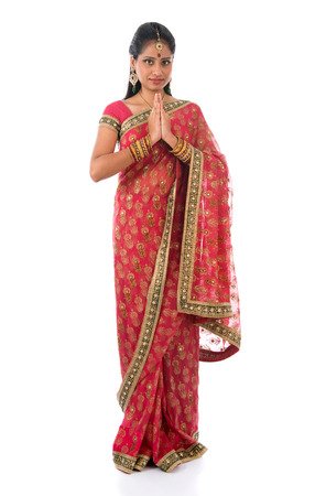 Indian girl in a greeting pose, traditional sari costume, full length standing isolated on white background photo