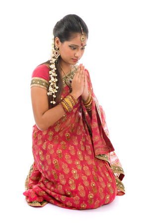 Indian girl in a greeting pose, traditional sari costume, full length kneeling on floor isolated on white background photo