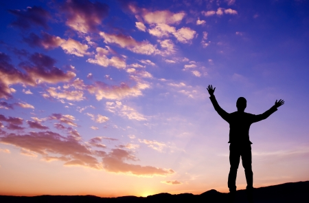 outstretch: Silhouette of businessman standing on top mountain open arms looking at the sunrise or sunset