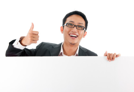 Blank paper for advertisement.  Young Asian executive male showing thumb up hand sign holding a white card board ready for text, isolated over white background. photo