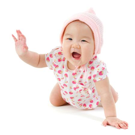 6 ヶ月古いアジアの女の子以上の分離した白色の背景をクロールします。