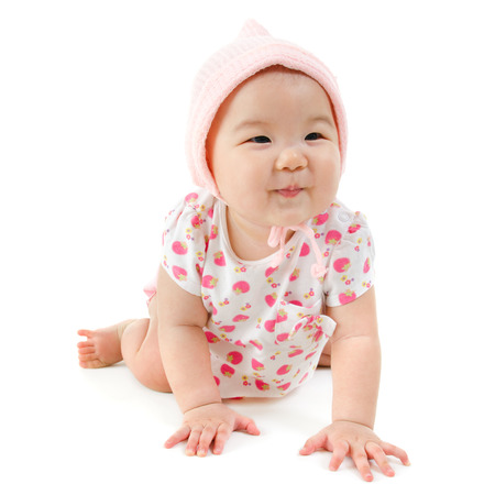 Six months old Asian mixed race baby girl crawling over white background, isolated. photo
