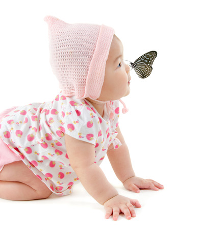 asian baby girl: Butterfly flying to Asian baby girl nose, isolated on white background