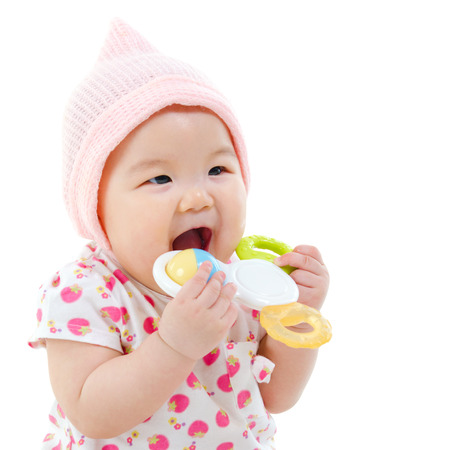teething: Beautiful mixed race Asian baby girl teething, biting with her toys, isolated on white background.