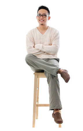 Full body Asian male sitting on a chair isolated over white background photo