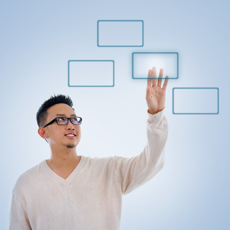 blue button: Asian man finger pressing on touch screen monitor button, isolated on blue background. Asian male model.