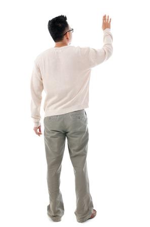 completo: Vista posterior de la mano del hombre asi�tico tocando en la pantalla virtual transparente, el espacio para el texto del bot�n , de cuerpo entero de pie aislado en fondo blanco.