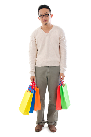 Bored Asian man shopper holding shopping bags waiting for his girlfriend standing isolated over white background photo