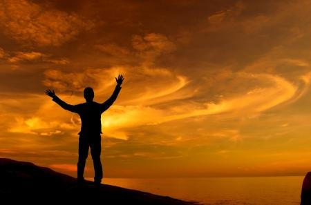 shadows: Silueta de hombre de negocios de pie en la roca frente al mar brazos abiertos mirando al cielo Foto de archivo