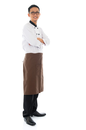 asian chef: Full body portrait of confident Asian chef arms crossed, smiling and standing isolated on white background. Stock Photo