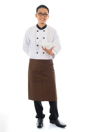 Full body Asian chef holding an empty plate, standing isolated on white background. photo