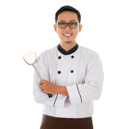 spatula: Portrait of Asian chef holding spatula, smiling and standing isolated on white background.
