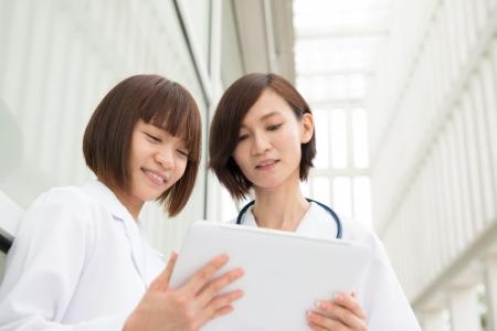 Aziatische artsen die discussie in het ziekenhuis corridor. Met behulp van digitale computer tablet.
