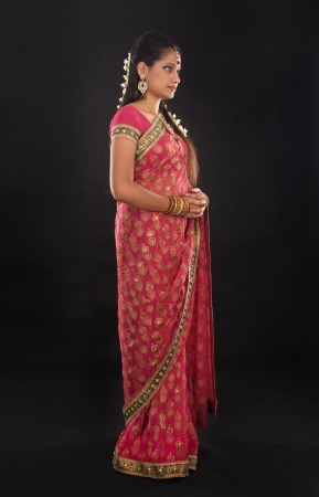 Full body traditional young Indian girl in sari costume standing isolated on black. photo