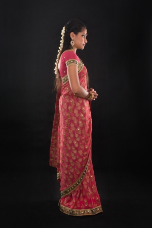 Full body side view or profile of traditional young Indian girl in sari costume standing isolated on black. photo