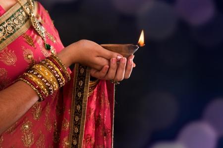 Diwali o Deepavali foto con le mani femminili in possesso di lampada ad olio durante la festa della luce