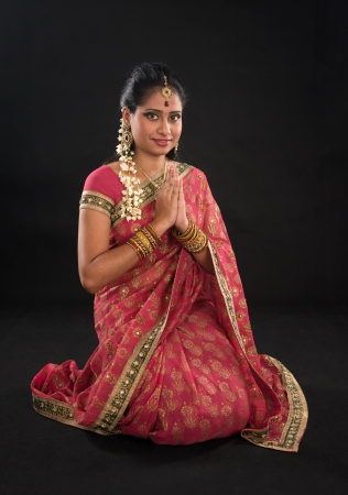 Indian girl in a greeting pose, traditional sari costume, full length kneeling on floor isolated on black. photo