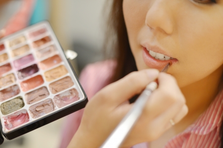 asian bride: Young beautiful Asian bride applying wedding make-up by make-up artist. Focus on lips.  Stock Photo