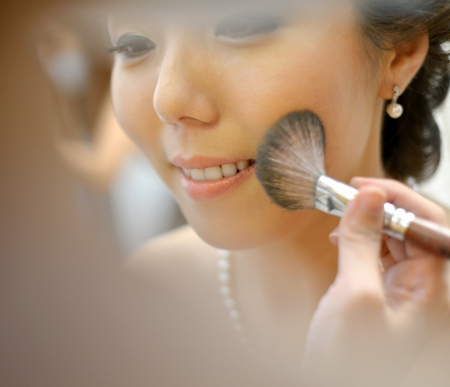 Beautiful Asian bride applying wedding make-up photo