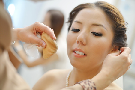 Beautiful Asian Chinese bride applying wedding make-up. photo