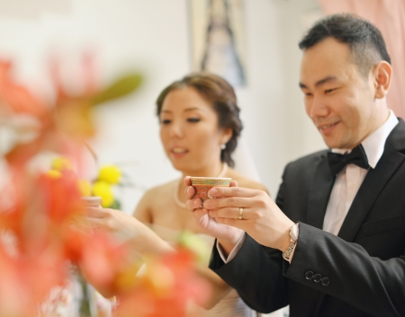 singapore culture: Traditional Chinese wedding tea ceremony, bride and groom, focus on hand and teacup. Stock Photo