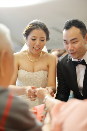Traditional Chinese wedding, bride and groom receiving gift from elders after tea serving. Stock Photo