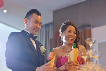 Happy Asian Chinese wedding dinner reception, bride and groom champagne toasting. photo