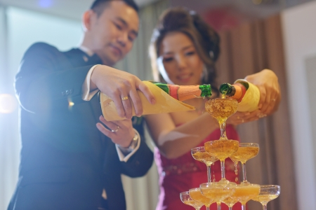 Asian Chinese wedding dinner reception, bride and groom champagne toasting.